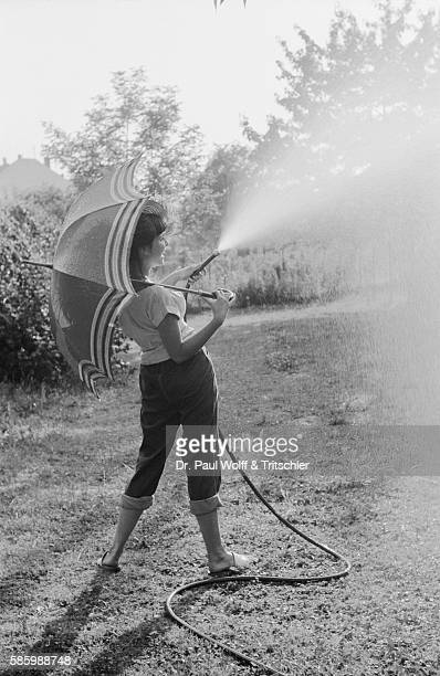 Young Woman with Umbrella Watering Lawn with Hose