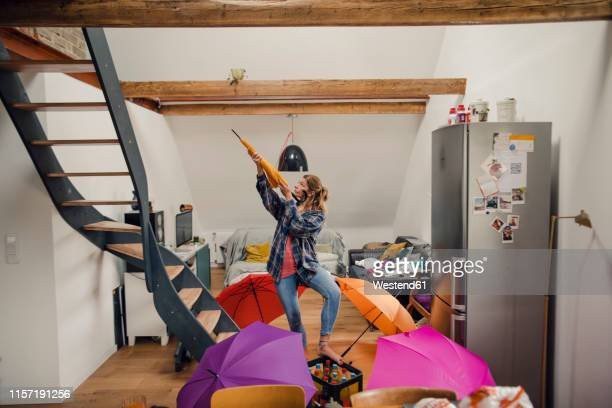 young woman with umbrellas at home - aiming stock pictures, royalty-free photos & images