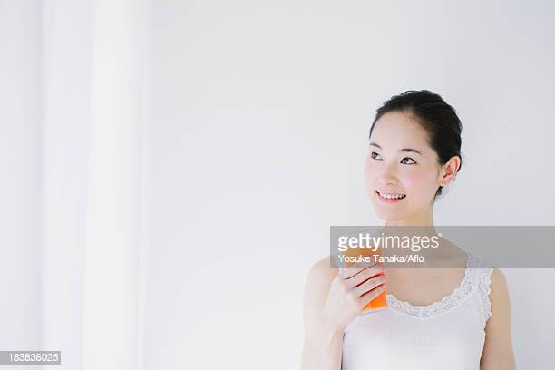 Young woman with vegetable juice smiling away