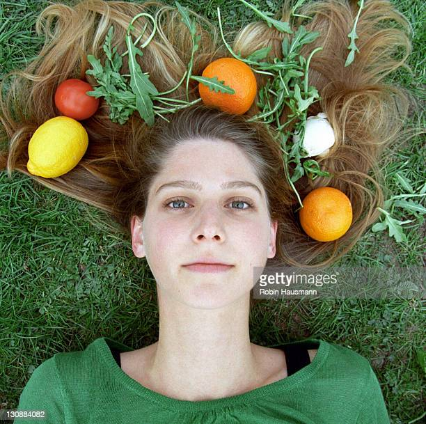 Young woman with vegetables and fruit in her hair