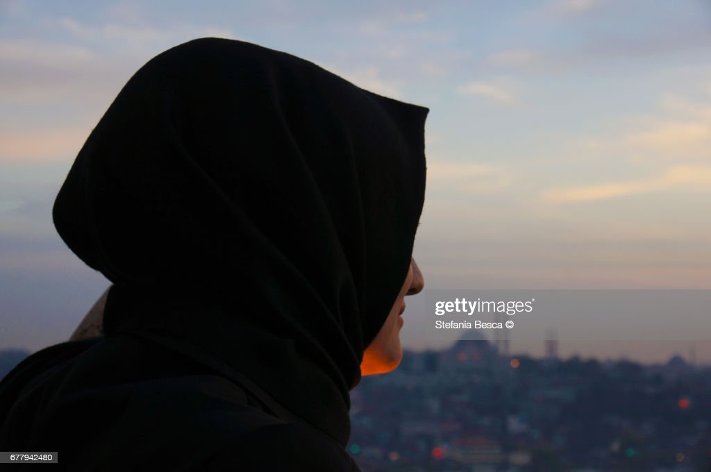 Young woman with veiled head looks at the panorama : Stock Photo