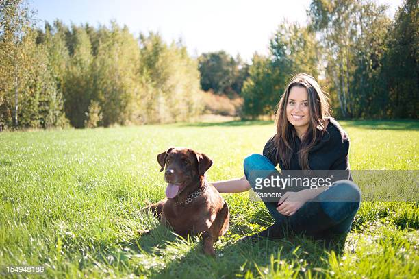 A young woman with views Labrador in the grass