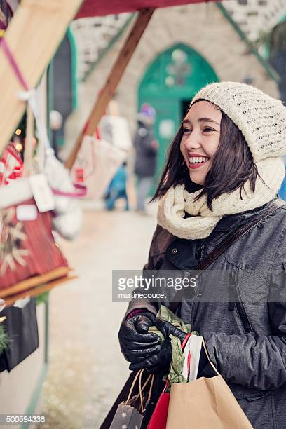 Young woman with wallet at outdoors Christmas market in winter.
