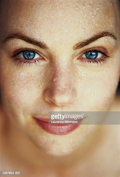 Young woman with water droplets on face, close-up