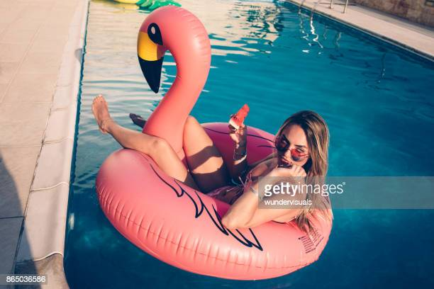 Young woman with watermelon floating on inflatable flamingo in pool