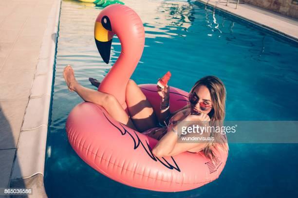 Junge Frau mit Wassermelone auf aufblasbare Flamingo im Pool schwimmen