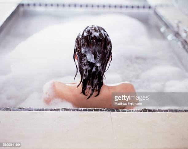 Young woman with wet hair sitting in a bath tub (back view)