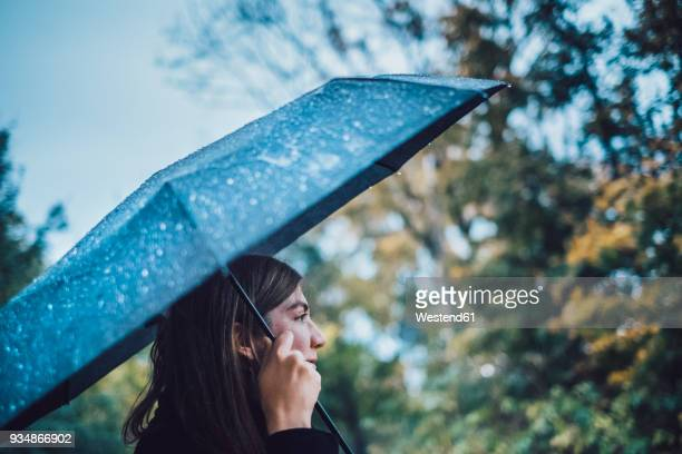 young woman with wet umbrella in autumnal park - elements stock photos and pictures