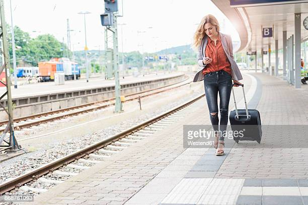 Young woman with wheeled luggage looking at her smartphone while walking at platform