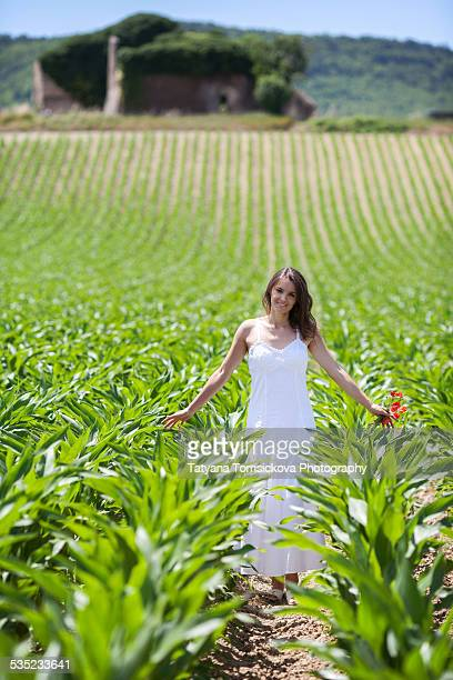 Young woman with white long dress in a corn field