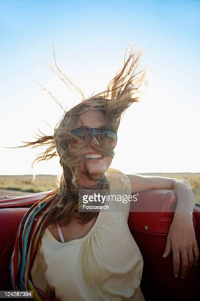 Young woman with wind swept hair in convertible
