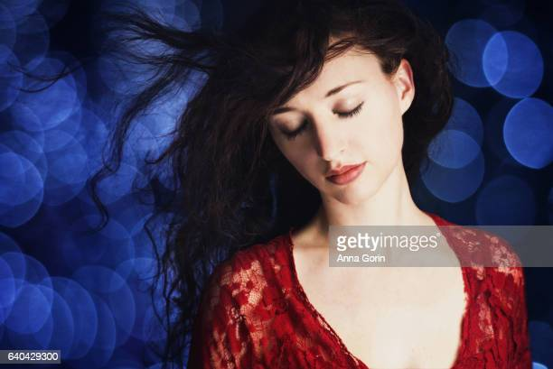 Young woman with windswept dark hair in red lace top, eyes closed, dark blue bokeh background
