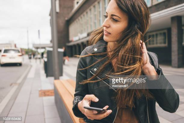 young woman with windswept hair holding cell phone in the city - lebensstil stock-fotos und bilder