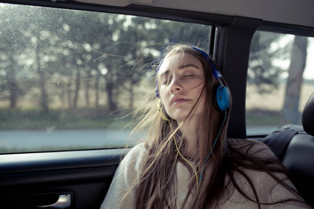 young woman with windswept hair in a car wearing headphones - listening to music in car stock pictures, royalty-free photos & images