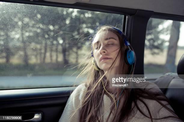 young woman with windswept hair in a car wearing headphones - landfahrzeug stock-fotos und bilder