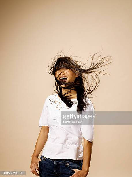 Young woman with windswept hair laughing