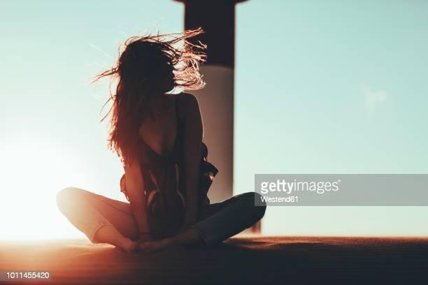 young woman with windswept hair sitting in desert landscape at sunset - gegenlicht stock-fotos und bilder