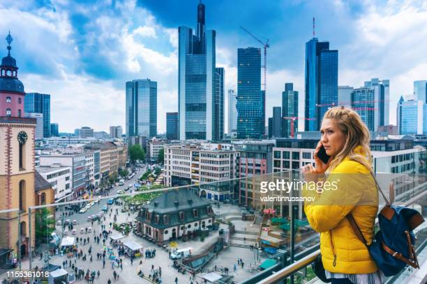 young woman with yellow jacket talking on a smart phone in front of skyline of modern frankfurt am main, germany - frankfurt main stock pictures, royalty-free photos & images