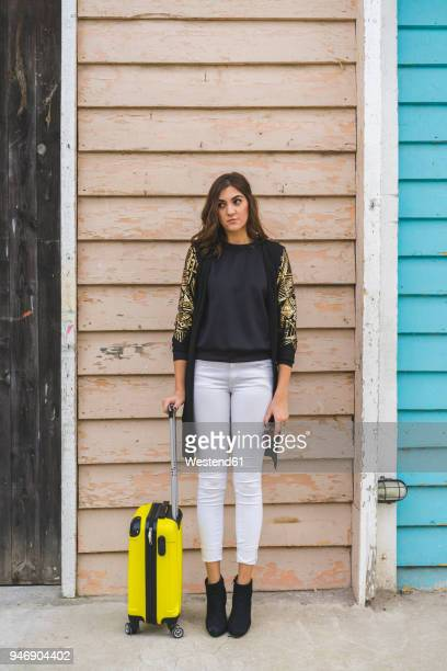 young woman with yellow trolley bag waiting in front of wooden facade - wheeled luggage stock photos and pictures