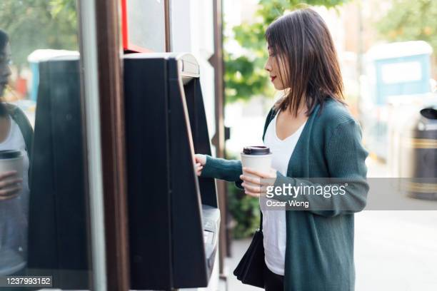 young woman withdrawing cash money at the atm - paying stock pictures, royalty-free photos & images