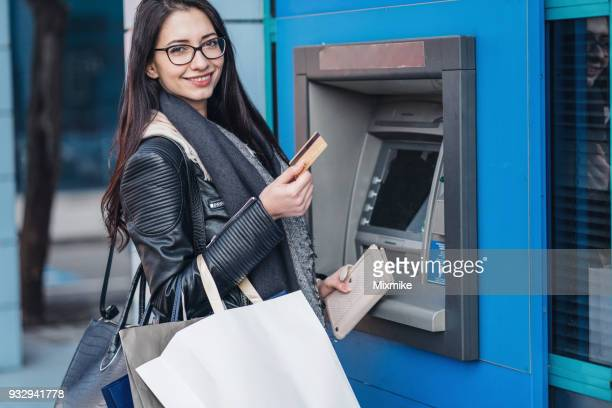 Young woman withdrawing money from her bank card