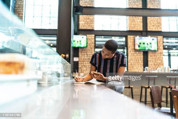 junge frau arbeitet und kopiert informationen im restaurant - nur erwachsene stock-fotos und bilder