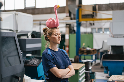 Young woman working as a skilled worker in a high tech company, balancing a pink flamingo on her head - gettyimageskorea