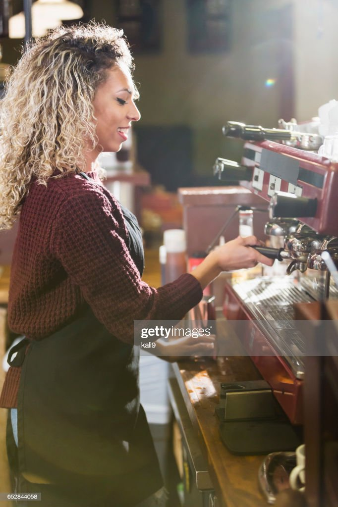 Young woman working as barista at coffee shop : Foto stock