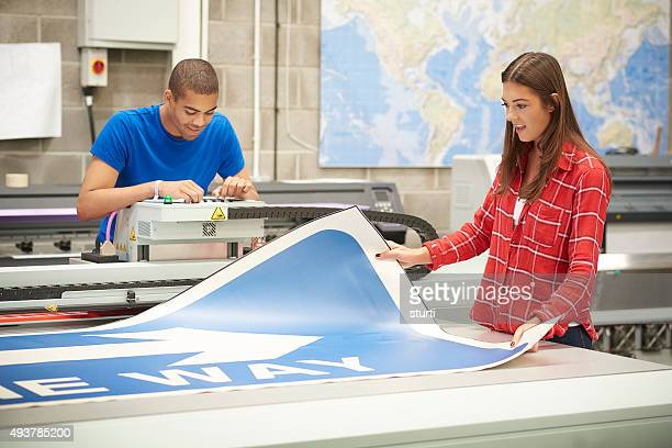 young woman working at a digital printers - printout stock pictures, royalty-free photos & images