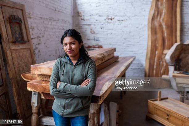 young woman working at artisanal furniture workshop - women stock pictures, royalty-free photos & images