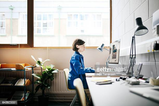 young woman working at computer in studio