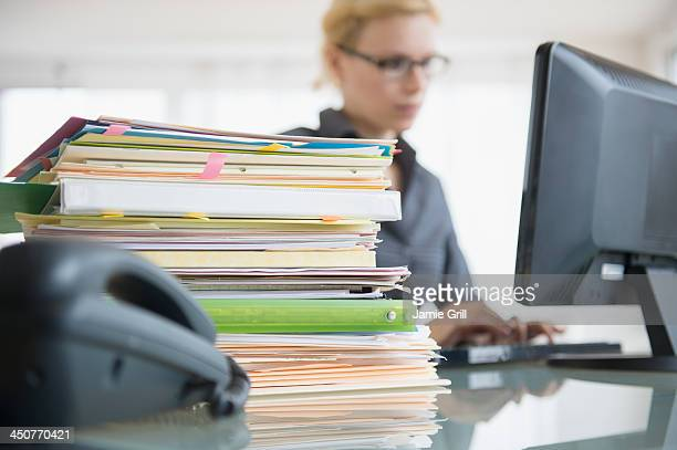 young woman working at desk in office - papierkram stock-fotos und bilder