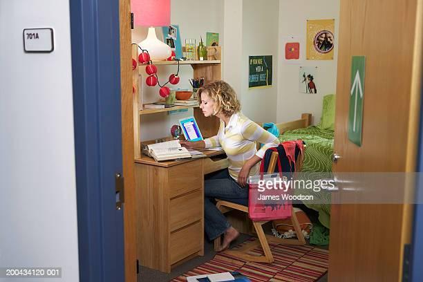 Young woman working at desk in student dorm, view through open door