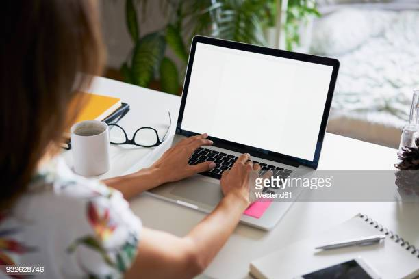 young woman working at desk with laptop - computermonitor stockfoto's en -beelden