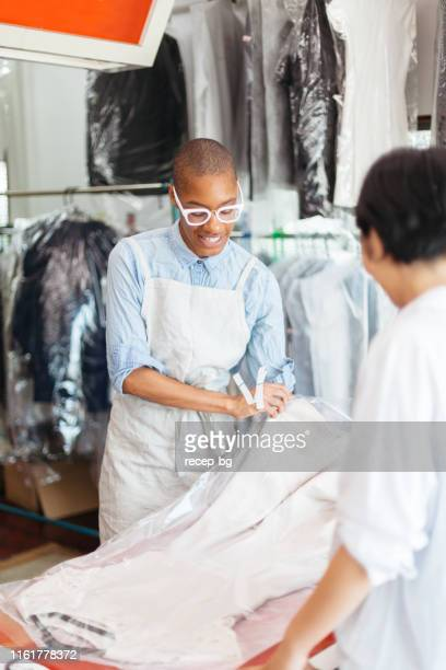 young woman working at dry cleaning shop and talking to costumer - dry cleaner stock pictures, royalty-free photos & images