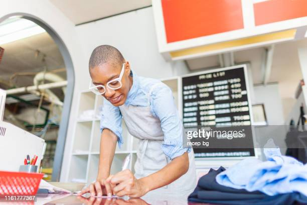 young woman working at dry cleaning shop - dry cleaner stock pictures, royalty-free photos & images