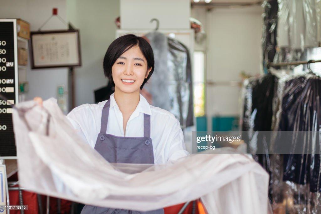 ドライクリーニング店で働く若い女性 : ストックフォト