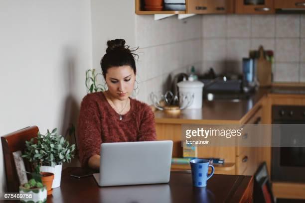 アパートで彼女のラップトップで働く若い女性 - 若い女性だけ ストックフォトと画像
