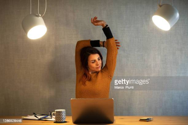 young woman working at home with laptop arms stretched - human body part stock pictures, royalty-free photos & images