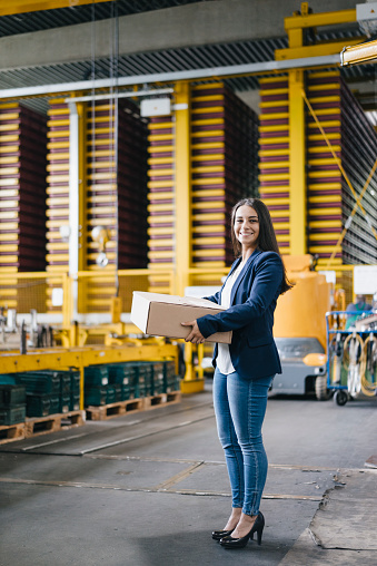Young woman working at parcel service, carrying parcel in warehouse - gettyimageskorea