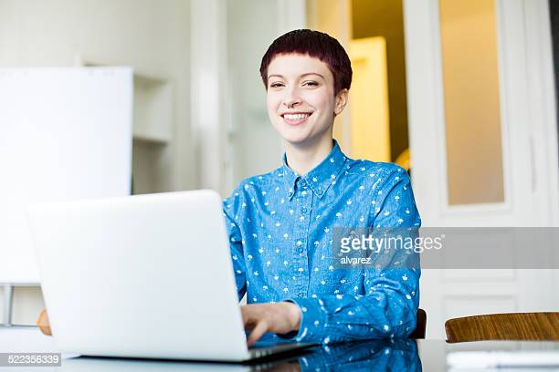 Young woman working at startup looking happy