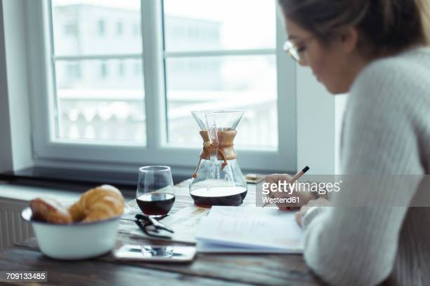 young woman working at table at home - food journal stock-fotos und bilder