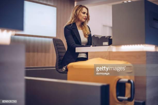 Junge Frau am Flughafen Check-in-Schalter