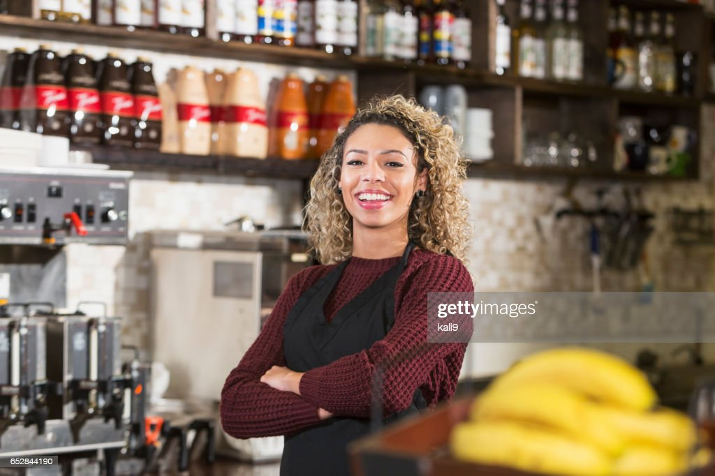 Young woman working behind counter at coffee shop : Stock Photo