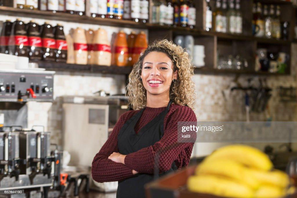 Jonge vrouw achter balie werken bij koffiehuis : Stockfoto