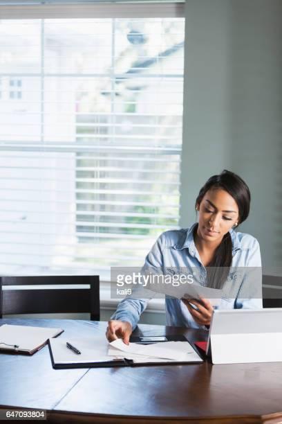 jovem mulher trabalhando em casa ou pagar contas - pilha arranjo - fotografias e filmes do acervo
