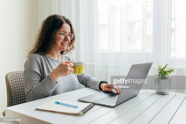 young woman working from home - makeshift stock pictures, royalty-free photos & images