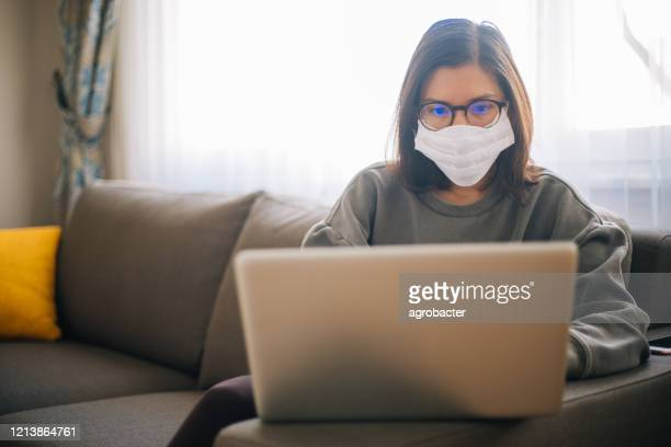 young woman working from home wearing protective mask - pandemic illness stock pictures, royalty-free photos & images