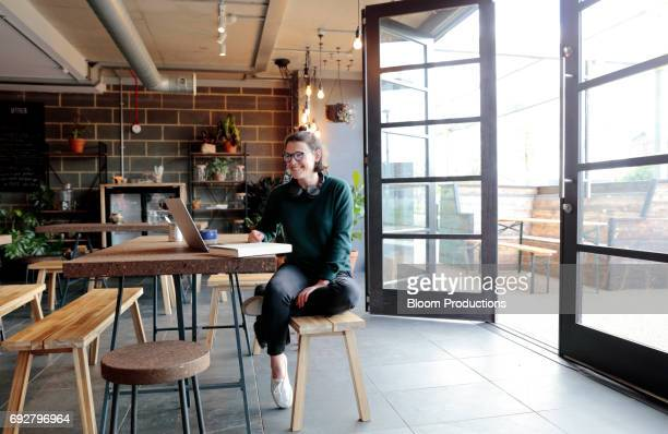 Young woman working in a cafe, wearing headphones and using a laptop