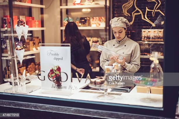 Jeune femme travaillant dans une boutique de chocolats